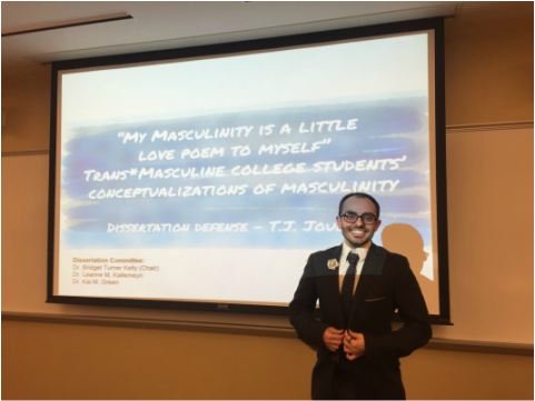 Picture of T.J. Jourian standing in front of a Powerpoint slide. The slide is the title of his dissertation defense (