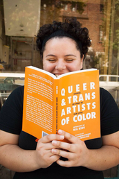 Picture of Nia King holding an open copy of